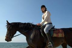 Montar a caballo de lomo de caballo de la mujer en la playa Imagen de archivo libre de regalías