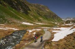 Montar a caballo de Mountainbikers en las montañas Foto de archivo