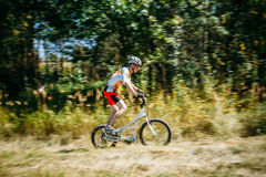 Montar a caballo de pasos del ciclista de la bici en bosque en el día soleado Foto de archivo