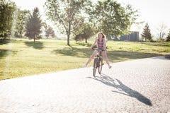 Montar a caballo de risa de la muchacha en la bicicleta Fotografía de archivo