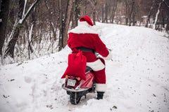 Montar a caballo de Santa Claus en la vespa Foto de archivo