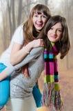 Montar a caballo del adolescente en su hermana sobre bosque Imagen de archivo