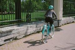 Montar a caballo del adolescente en una calle con una bicicleta Fotografía de archivo