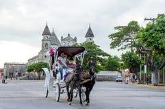 Montar a caballo del carro del caballo más allá de la iglesia de Merced del La, Granada Nicaragua Imagenes de archivo