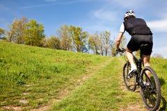 Montar a caballo del ciclista de la bici de montaña cuesta arriba Imagenes de archivo