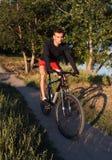 Montar a caballo del ciclista de la bici de montaña en hacer sano de la forma de vida de la salida del sol Imagen de archivo libre de regalías
