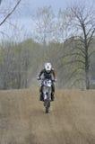 Montar a caballo del corredor del motocrós abajo de una colina de la suciedad Imagen de archivo