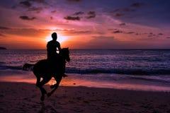 Montar a caballo del hombre de la silueta Fotografía de archivo