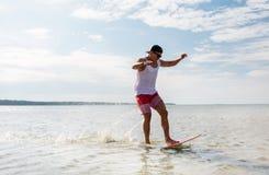 Montar a caballo del hombre joven en skimboard en la playa del verano Fotos de archivo libres de regalías