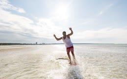 Montar a caballo del hombre joven en skimboard en la playa del verano Imagen de archivo libre de regalías