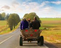 Montar a caballo del hombre y de la mujer en un carro Fotos de archivo libres de regalías
