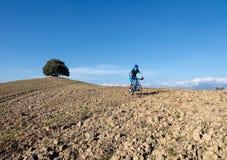Montar a caballo del motorista de la montaña con paisaje toscano Fotos de archivo