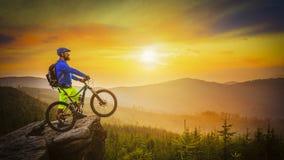 Montar a caballo del motorista de la montaña en la puesta del sol en la bici en las montañas del verano delanteras foto de archivo libre de regalías