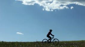 Montar a caballo del motorista de la montaña a través de un prado almacen de video