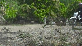 Montar a caballo del motorista en el camino del campo Motorista de Moto que conduce en la rueda posterior en apagado camino Depor metrajes
