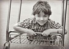 Montar a caballo del muchacho en el carro de la compra Foto de archivo