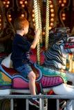 Montar a caballo del muchacho en el carrusel foto de archivo