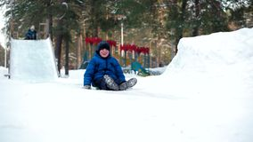 Montar a caballo del muchacho en el trineo con la montaña rusa de madera en parque del invierno almacen de video