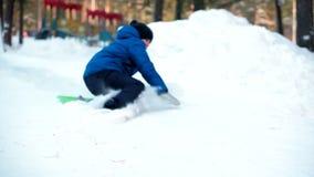 Montar a caballo del muchacho en el trineo con la montaña rusa de madera en parque del invierno metrajes