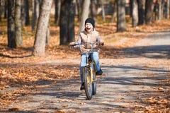 Montar a caballo del muchacho en la bicicleta, parque de la ciudad del otoño, día soleado brillante, hojas caidas en fondo Fotografía de archivo libre de regalías