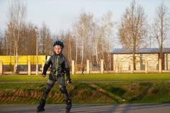 Montar a caballo del muchacho en pcteres de ruedas en el parque Fotografía de archivo libre de regalías