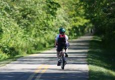 Montar a caballo del niño en el camino de la bici imágenes de archivo libres de regalías