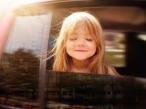 Montar a caballo del niño en el coche que mira hacia fuera la ventana Fotos de archivo