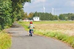 Montar a caballo del niño en la bicicleta el día de verano en país Foto de archivo libre de regalías