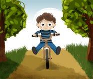 Montar a caballo del niño en una bicicleta Imagenes de archivo