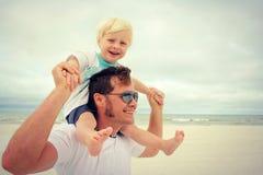 Montar a caballo del niño joven en los hombros del padre feliz en la playa Imagen de archivo libre de regalías