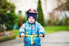 Montar a caballo del niño pequeño con su primera bicicleta al aire libre Foto de archivo libre de regalías