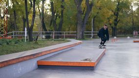 Montar a caballo del skater del inconformista y salto en un parque del patín Tiro a cámara lenta almacen de video