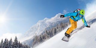 Montar a caballo del snowboarder del hombre en cuesta imagen de archivo libre de regalías