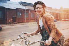 Montar a caballo elegante de la mujer en la bici Imagen de archivo libre de regalías