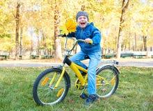 Montar a caballo en la bicicleta en parque del otoño, día soleado brillante, hojas caidas del muchacho en fondo Imágenes de archivo libres de regalías