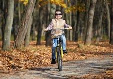 Montar a caballo en la bicicleta en parque del otoño, día soleado brillante, hojas caidas del muchacho en fondo Imagen de archivo