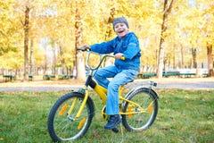 Montar a caballo en la bicicleta en parque del otoño, día soleado brillante, hojas caidas del muchacho en fondo Foto de archivo