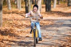 Montar a caballo en la bicicleta en parque del otoño, día soleado brillante, hojas caidas del muchacho del niño en fondo Fotos de archivo