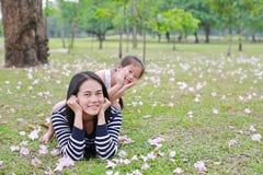 Montar a caballo feliz de la niña en la parte posterior su mamá que miente en campo verde con completamente la flor del rosa de l fotografía de archivo