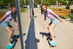 Montar a caballo feliz del adolescente en longboard en verano Foto de archivo libre de regalías