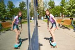 Montar a caballo feliz del adolescente en longboard en verano Fotos de archivo libres de regalías