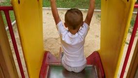 Montar a caballo feliz del niño con una diapositiva de los niños Visión desde arriba Juegos de niños en el patio almacen de video