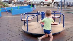 Montar a caballo feliz del niño en el carrusel Un muchacho está jugando en el patio metrajes
