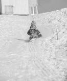 Montar a caballo feliz del niño en una colina nevosa en invierno Foto de archivo libre de regalías
