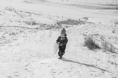 Montar a caballo feliz del niño en una colina nevosa en invierno Foto de archivo