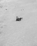 Montar a caballo feliz del niño en una colina nevosa en invierno Fotografía de archivo
