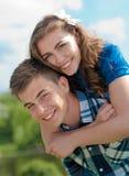 Montar a caballo feliz: pares jovenes sonrientes y cielo azul Imagen de archivo libre de regalías