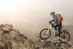 Montar a caballo femenino del motorista en la bicicleta en montañas imagen de archivo libre de regalías