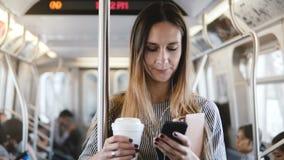 Montar a caballo femenino hermoso relajado feliz del freelancer en el tren del metro que mira smartphone usando la sonrisa del ap almacen de metraje de vídeo