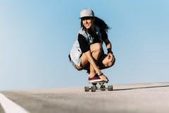 Montar a caballo hermoso de la mujer del patinador en su longboard Foto de archivo libre de regalías
